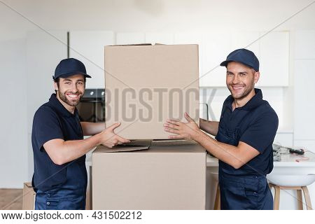 Movers Smiling At Camera While Stacking Carton Packages In Kitchen