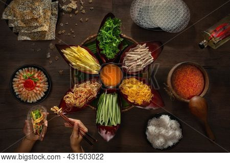 Lau. Hot pot with pork, banana flowers, mango, salted fish, scrambled eggs, rice noodles - Vietnamese cuisine. Female hands collect ingredients in a cake