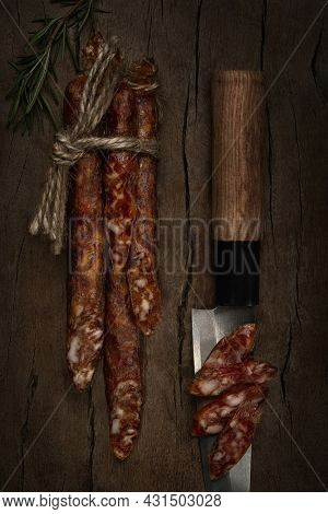 Smoked hunter sausages and slices on knife's blade continuing shape of it with rosmarine on wooden background