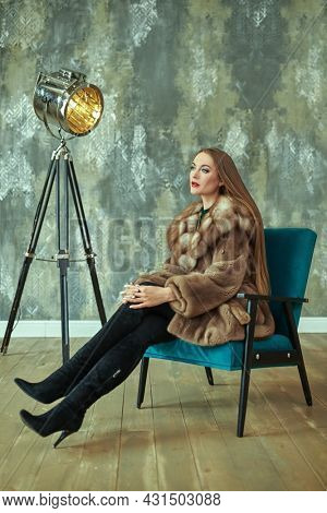 Fur coat fashion. Beautiful glamorous woman in an expensive fur coat posing in luxury apartments. Full length portrait.