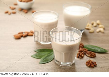 Different Vegan Milks And Nuts On Wooden Table, Closeup
