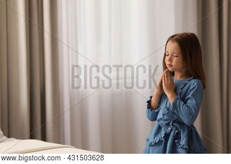 Cute Little Girl Saying Bedtime Prayer At Home. Space For Text