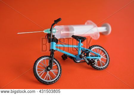 Bike Model And Syringe On Red Background. Using Doping In Cycling Sport Concept