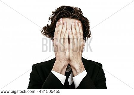 People, emotions. Portrait of a well-groomed man in black suit covering his face with his hands. Studio shot on a white background.