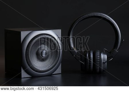 Black Single-way Speaker With One Speaker And Black Headphones With Ear Pads On A Black Background.