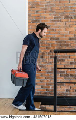 Young Workman With Toolbox And Flashlight Walking Downstairs In Apartment