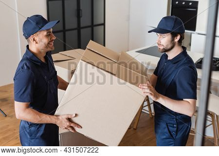 Smiling Mover Holding Carton Box With Colleague In Kitchen