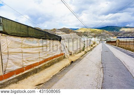 Spanish Landscape With Asphalt Road Between Plastic Greenhouses. Almeria Region, Andalusia Spain.