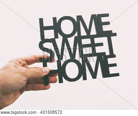 Hand holds wooden phrase Home sweet home. Concept of buying or building home of dreams
