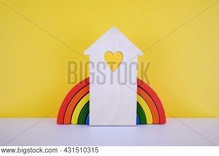 Wooden Icon-house On The Background Of A Wooden Toy Rainbow On A Yellow Background.rent, Purchase Of