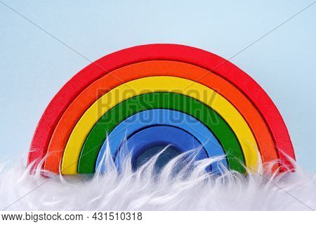 A Wooden Toy Rainbow On A Blue Background,with White Fur Like A Cloud At The Bottom.montessori Conce