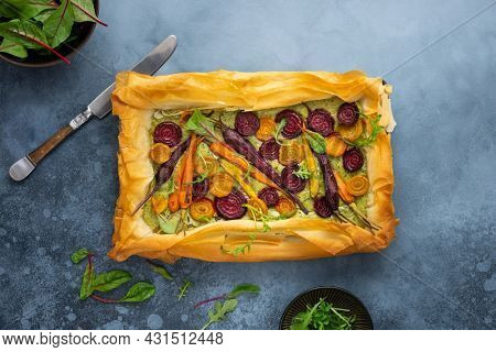 Carrot and Beet Tart with pesto and phyllo dough. Savoury vegetable baking. Homemade vegetarian food.Top view.
