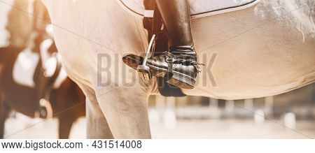 A White Horse Is Wearing A White Saddlecloth And Stirrup, And A Rider In Black Boots With Spurs Is S