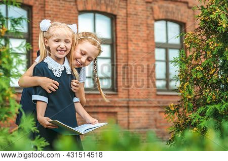 Two Cheerful Schoolgirls Are Holding A Book In Their Hands. The First Day At School. Concept On The