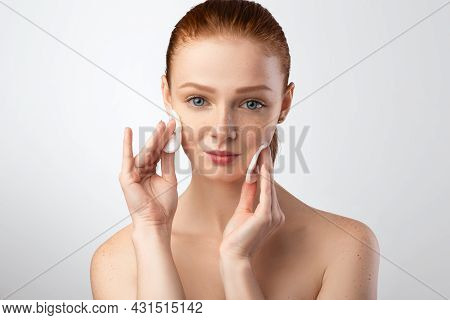 Red-haired Young Woman Cleansing Skin Using Cotton Pads In Studio