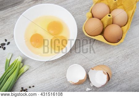Three Eggs Broken, Green Onions, Eggs In A Package, Black Peppercorns For Cooking. Ingredient In The