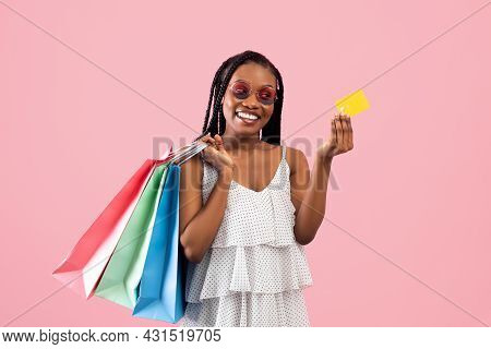Easy Shopping. Joyful Afro Lady Holding Credit Card And Bright Shopper Bags On Pink Studio Backgroun