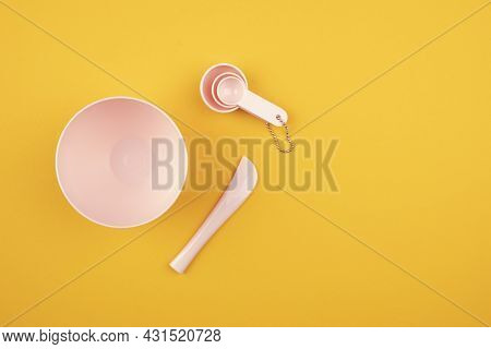 Pink Set For A Face Mask On An Orange Background. Plastic Bowl And Spoons For Spa Hair Care Treatmen