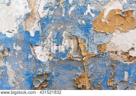 The Texture Of The Peeling And Cracked Yellow And Blue Paint On The Old Wall
