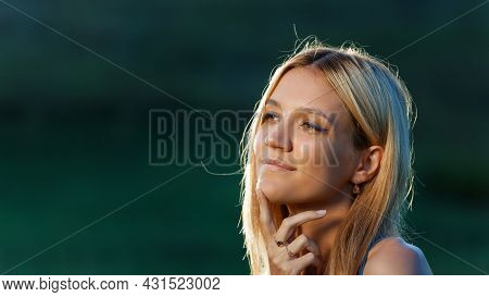 Portrait Of A Young Attractive Girl With Contemplative Look In Backlight Against Blurred Background.