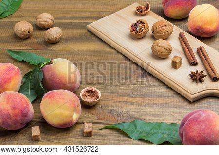 Ripe Peaches With Green Leaves On Table. Walnuts, Cinnamon Sticks And Star Anise On Board. Wooden Ba