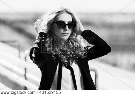 Young business woman in sunglasses walking on city street Stylish fashion model in black jacket and sunglasses