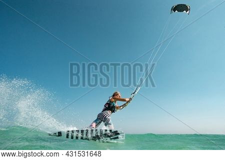 Kite surfer woman rides with kiteboard  in transition