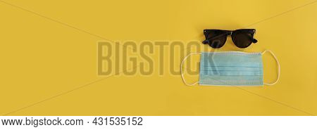 Sunglasses And Medical Mask On The Yellow Background. Free Space For Text, Copy Space. Vacation Back