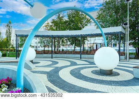 A Modern City Park With A Light Fountain In The Form Of White Balls And A Pavilion With Concrete Ben