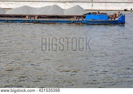 A Barge Loaded With Gray Rubble Floats Along The River. At The Top Of The Picture