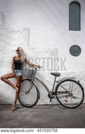Portrait of pretty sexy looker young girl in jeans shorts posing on white wall background with bicycle . Outdoor.