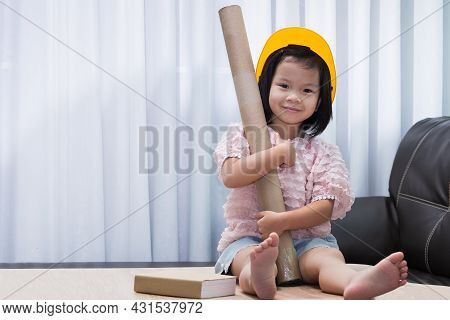 Portrait Of Asian Child Girl Wearing Yellow Helmet Safety Hat. Kid Holding Paper Cylinder For Work.