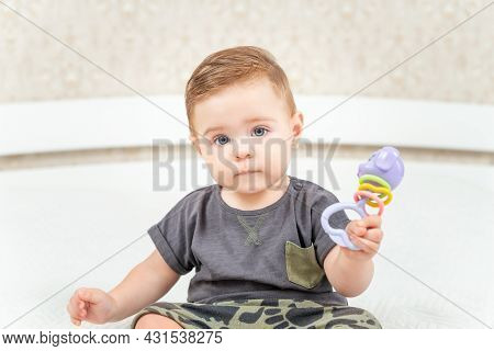 Charming Baby. Baby Boy Playing With Toy Rattle Sitting On A Bed. Little Child Looking At Camera.