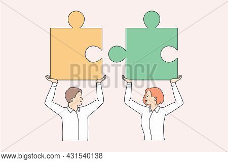 Teamwork And Collaboration In Business Concept. Young Man And Woman Partners Holding Huge Pieces Of