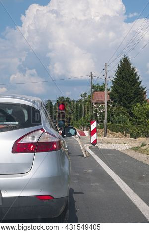 Road Works In Progress. The Car Is Stopped In Front Of The Road Construction Traffic Light. The Traf
