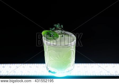 Fresh Green Kiwi Kick Alcohol Cocktail Drink In Wineglass On Black Background