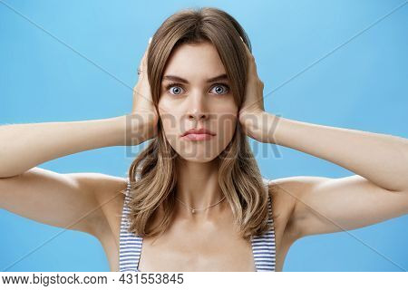 Close-up Shot Of Intense Irritated Displeased Young Attractive Woman Closing Ears With Palms Frownin