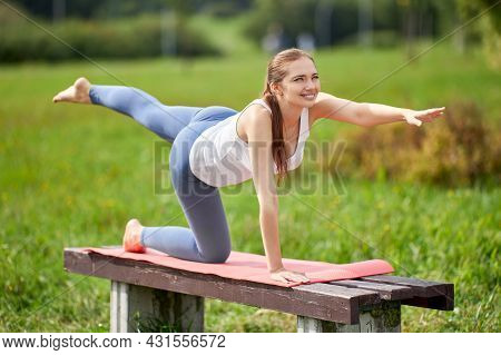 Cheerful Woman Trains Yoga On Park Bench.