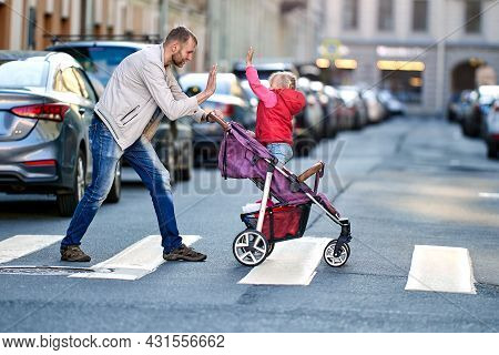 Man Plays With Little Daughter In Baby Carriage On Crosswalk Near Traffic.