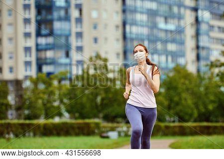 Woman In Protective Facial Mask Runs Outdoors.