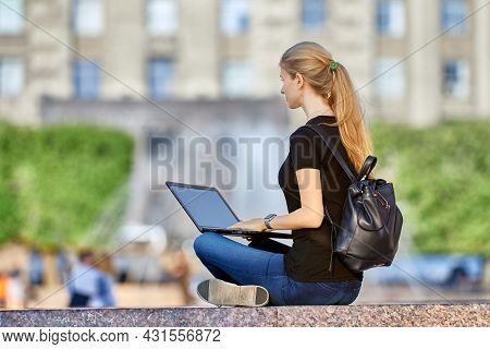 Remote Work By Woman With Laptop In City Garden.