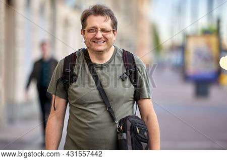Middle Aged Man With Cross Body Bag And Backpack Outdoors.