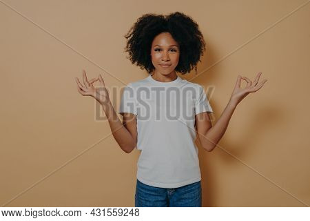 Mindfulness Concept. Peaceful Afro American Young Woman In Casual Outfit Keeping Hands In Mudra Gest