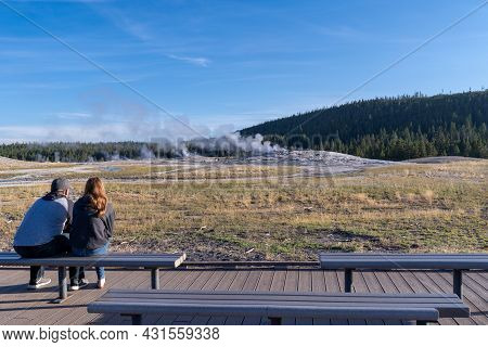 Wyoming, Usa - August 11, 2021: Young Couple Waits On The Benches For Old Faithful To Erupt In The M