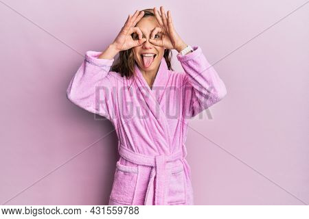 Young blonde woman wearing bathrobe doing ok gesture like binoculars sticking tongue out, eyes looking through fingers. crazy expression.