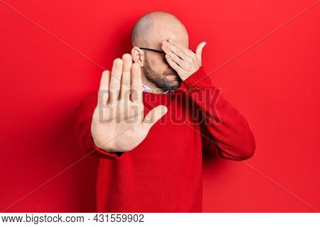 Young bald man wearing casual clothes and glasses covering eyes with hands and doing stop gesture with sad and fear expression. embarrassed and negative concept.