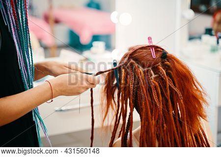Girl Hairdresser Weaves Woman Ginger Dreadlocks And Cut Threads With Scissors. Braiding Process Plai