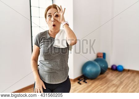 Middle age woman wearing sporty look training at the gym room doing ok gesture shocked with surprised face, eye looking through fingers. unbelieving expression.