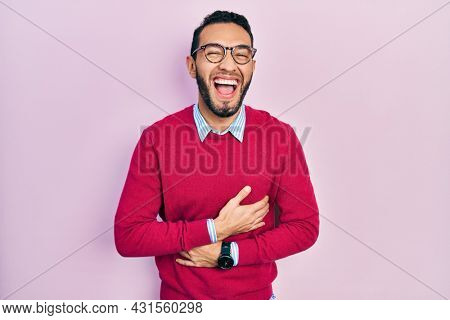Hispanic man with beard wearing business shirt and glasses smiling and laughing hard out loud because funny crazy joke with hands on body.