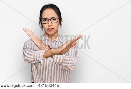 Young hispanic girl wearing casual clothes and glasses rejection expression crossing arms doing negative sign, angry face